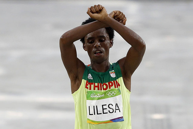 """Image of Lilesa Feyisa, Ethiopian long-distance runner, performing his politically-charged """"X"""" gesture."""