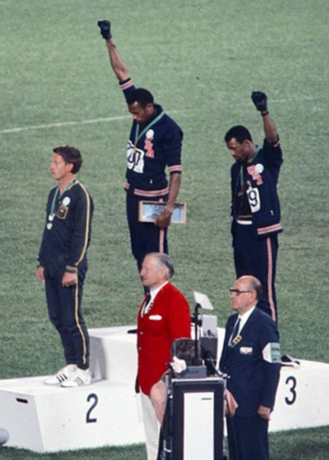 "Tommie Smith (centre) and John Carlos (right) raise their fists whilst on the dais in the political ""Black Power"" protest at the 1968 Olympic Games."