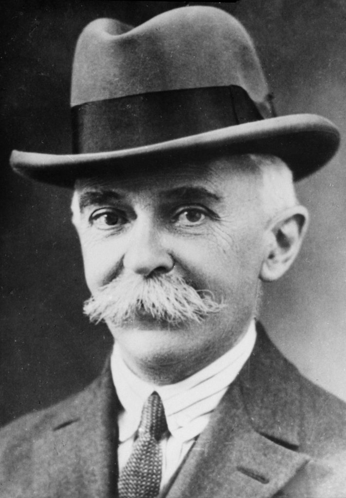 Pierre de Coubertin, with a large hat and moustache - the man who brought together politics and sport in the Olympic Games.