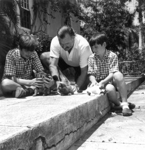 Hemingway playing with cats with his sons.